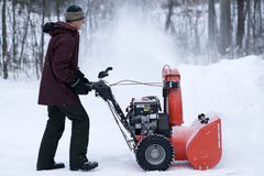 Man Operating Snow Thrower in Driveway stock photo