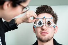 Man with optician at eyesight test for glasses Stock Photos