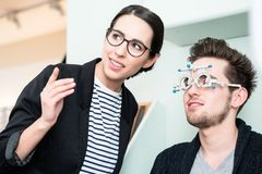 Man with optician at eyesight test for glasses. In optician shop Stock Photography