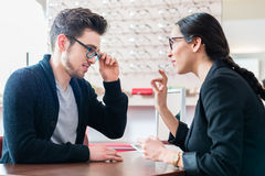 Man in optician shop getting advice from saleswoman Stock Photos