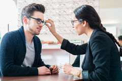 Man in optician shop getting advice from saleswoman Stock Photography