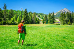 Man with orange backpack and mountain peaks Stock Images