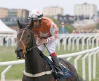 Man in orange clothes riding a race horse Stock Photos