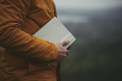 Man in Orange Coat Holding Beige Cover Book Royalty Free Stock Images