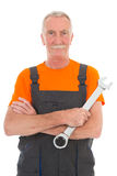 Man in orange and gray overall with wrench Stock Image