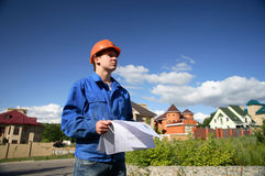 Man in a orange helmet with the plan of construction. Man in a orange helmet Royalty Free Stock Images