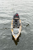 The man in the orange kayak to catch fish. He wears a black hood. Stock Image
