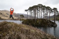 Man in Orange Long-sleeved Shirt Jumping on Lake Near Tall Trees at Daytime royalty free stock photos