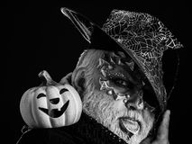 Man with orange pumpkin. Wizard in witch hat on black background. Jack o lantern with spooky smile. Magic and halloween concept. Sorcerer with dragon skin and royalty free stock images