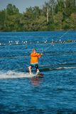Man, in orange shirt and helmet, is practicing wakeboarding. In a cable park on a sunny day. Active vacation in outdoor Royalty Free Stock Image