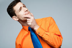 Man in orange shirt thinking about problem. Stock Images