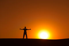 Heroic achievement by men. Man at orange sunset in desert with heroic achievement gesture Royalty Free Stock Images