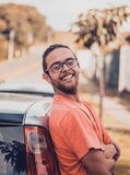 Man in Orange T-shirt Leaning on a Car Royalty Free Stock Photos