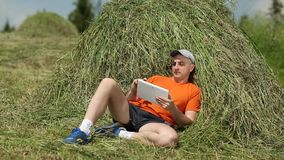 Man in orange T-shirt lying on haystack, watching gadget stock video