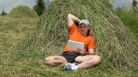 Man in orange t-shirt with tablet PC sits near a haystack stock video footage