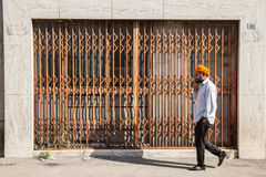 Man with orange turban in front of shuttered shop Royalty Free Stock Photo