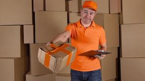 Man in orange uniform delivering heavily damaged parcel to customer. Brown cartons background. Unprofessional work and. Man in orange uniform delivering heavily royalty free stock images
