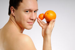 The man with oranges. The man with two fresh bright oranges Royalty Free Stock Images