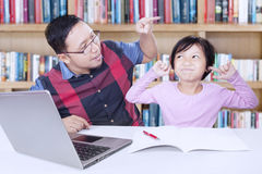 Man ordering a child to study. Image of young men scolding a little girl to learn and doing assignment in the library Royalty Free Stock Photo