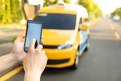 Man orders  taxi from his cell phone Royalty Free Stock Photography