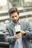 Man orders a taxi from his mobile phone Stock Image