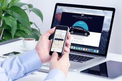 Man orders Uber by iPhone and Macbook with website on background. Varna, Bulgaria - May 29, 2015: Man orders Uber X through his iPhone and Macbook with Uber Royalty Free Stock Images