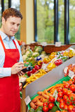Man in organic food store ordering vegetables. With mobile data acquisition terminal royalty free stock photos