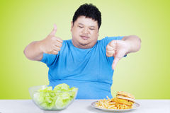 Man with organic salad and burger. Portrait of overweight person showing thumb up at the salad and thumb down at the burger Stock Photo
