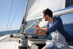 Man orienting the sails on a boat Stock Photo