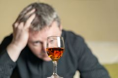 Man out of focus looks at a glass of brandy royalty free stock photography