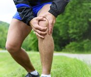 Man out jogging with knee pain Stock Photography