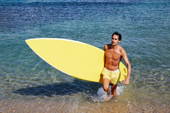 A man out of the water to bask in the sun. Half length portrait of mature man with abdominal coming out from the sea holding big copy space surfing board stock photography