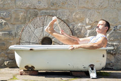 Man in the outdoor bathtub. Washes his leg stock photos