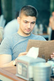 Man in outdoor restaurant looking at the menu Royalty Free Stock Image