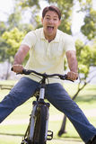 Man outdoors on bike with legs out Stock Images