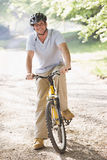 Man outdoors on bike smiling. At camera stock image