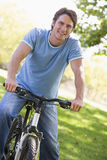 Man outdoors on bike smiling. At camera stock photos