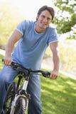 Man outdoors on bike smiling Stock Photos