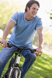 Man outdoors on bike smiling. Away from camera royalty free stock image