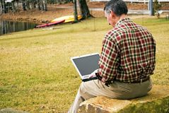 Man Outdoors with Computer. View of a man with a laptop sitting outdoors at a lake. He may be working, relaxing or looking for employment royalty free stock photo