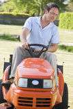 Man outdoors driving lawnmower. In garden royalty free stock photos