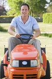 Man outdoors driving  lawnmower smiling Stock Image