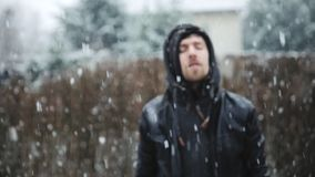 Man outdoors in falling snow slow motion footage. Man outdoors in falling snow closeup slow motion footage stock video footage