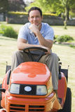 Man outdoors on lawnmower smiling. At camera royalty free stock photo