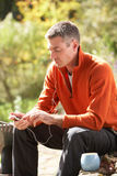 Man Outdoors Listening To MP3 Player. Whilst On Break From Gardening royalty free stock image