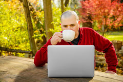 Man outdoors looking at Laptop and Drinking Coffee. A Man in a red shirt outdoors looking at Laptop and Drinking Coffee Royalty Free Stock Image
