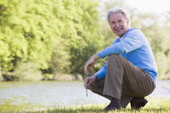 Man outdoors at park by lake smiling Stock Photography