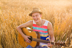 Man outdoors playing acoustic guitar Stock Image