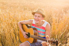 Man outdoors playing acoustic guitar Royalty Free Stock Photo