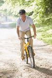 Man outdoors riding bike smiling royalty free stock photo